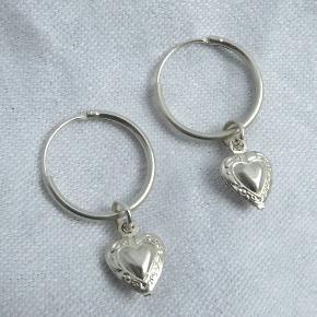Små hoops med hjertevedhæng. Hoopsene er i 925 sterling sølv og er 1,8 cm i diameter, hele længden er 3,3 cm.   Se også mine andre annoncer med smykker 🍀