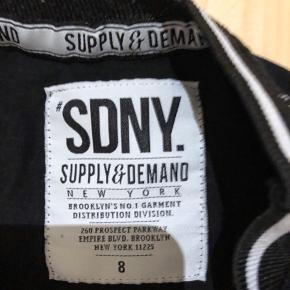 T-shift med logo; SDNY. Nederste del er mesh-lignende.