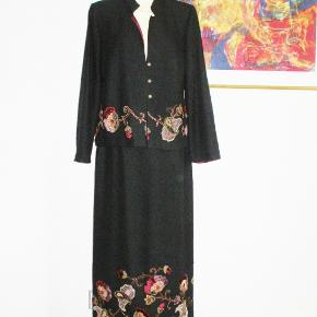 Designer Kirsten Krog: 2-delt sæt   -såå flot  Smuk jakke og lang nederdel med flot broderi og med små perler. Delene kan bruges hver for sig. Materialet er fint blødt 100 % uld  Oprindelig købspris: 2495 kr.  Jakken, som er med vinrød foer i polyester har  Brystvidde: 57 cm x 2 Længde: 62 cm  Nederdelen har sort foer og en 25 cm høj slidse midt bag.  Livvidde: 39-41 cm x 2 (pga elastik i linningen) Længde: 97 cm (kan lægges yderligere 3 cm ned hvis ....)  Ingen byt, og prisen er fast.