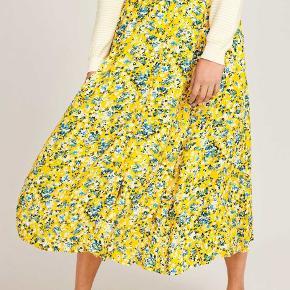 Smuk nederdel fra Samsøe Samsøe. Nederdelen er gul med en mønster af små blå, hvide og grønne blomster. Nederdelen er en løs model med masser af vidde, der falder super flot og let, når den kommer på. Lavet af 100% Viskose.   Nypris 900 kr