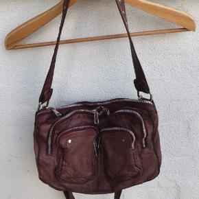 Jeg sælger min elskede taske.  Crossover taske fra Núnoo Jeg har taget billeder inde og ude, så jeg håber at det giver et billed af den fin farve.  Brede 40 cm Højde 28 cm Dybde 7.5 cm