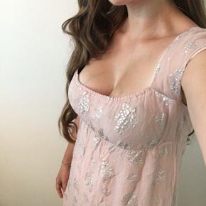 Smuk romantisk maxikjole med halv-gennemsigtige ærmer. Ærmerne kan sættes både oppe som på billedet, eller som cold shoulder ærmer. Kjolen er gammelrosa med sølv mønster, virkelig smuk. Husker ikke om jeg nåede at bruge den, men den passer desværre ikke længere.