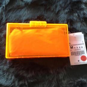 Varetype: Neon Orange Clutch Størrelse: Alm Farve: Neon Orange  Billederne drillede lidt, så tjek evt farven på nettet. Den er helt neon orange. Der er en lille taske indeni, så man ikke kan se, hvad man har i den, men den kan tages ud. Mål: Ca.18 cm lang Ca.10 cm høj Ca.4 cm bred/dyb  ALDRIG BRUGT - STADIG MED TAGS OG I DUSTBAG - BYTTER IKKE  Generelt: Hvis I ønsker mine ting sendt som forsikret pakke og/eller i boblekuvert/æske, så oplys venligst dette, så det kan lægges oveni prisen.