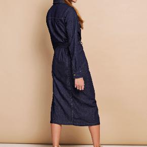 Skjortekjole i en flot, mørk farve. Kjolen, der har et lige, let figursyet snit, har knaplukning hele vejen ned, bindebånd i taljen og brystlommer med klap. Kontrastsyningerne giver en autentisk retro-vibe og gør kjolen ekstra trendy. Længden midt bagpå er 118 cm i en størrelse small.  Aldrig brugt - ny pris 700 kr.  Bytter ikke - ved ts handel pålægges gebyret.
