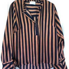Let skjorte med blå/bronze striber.  Sød detalje ved ærmer.  100% polyester