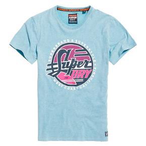 Acid T-Shirt I En Middelkraftig Kvalitet Med Grafik  Superdry Acid T-shirt i middelkraftig kvalitet med grafik til mænd. Klassisk T-shirt i blød bomuld, korte ærmer, rund hals og stor, tekstureret Superdry grafik på brystet. Læg dertil et Superdry logomærke på sømmen.  Style: M10101ST Bomuld 100% C