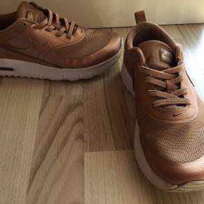 Fine Nike sneakers model Thea i kobber, søger nyt hjem. Er brugte, men i god stand. Ingen huller. Alm. Slidtage under sålen samt indersålen. Indvendig mål er 22 cm.