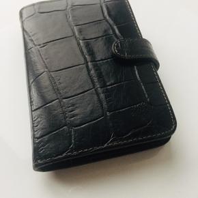 Tidløs kalender fra MULBERRY i sort læder. Kan også bruges som elegant notesbog. En klassiker der aldrig går af mode.  Str 10 x 15cm  Den fremstår som ny, intet slid eller ridser da den ikke er blevet brugt. Købes uden indmad.  Ønsker ikke at bytte.  KUN seriøse henvendelser, tak.  Afhentning Frederiksberg.