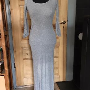 Maxikjole/midi kjole i fin ribstrikket bomuldsjersey. Grå, en enkelt brystlomme med knap detalje og opsmøg på ærmerne. Kan sende flere billeder. Mærket er Just Ginger, og den er købt i USA.