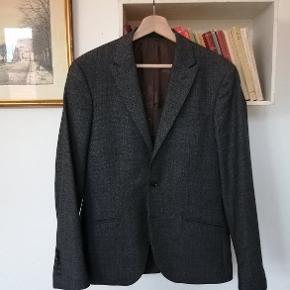 En fin jakke fra Bertoni i en farve der bedst beskrives som salt&pepper. På afstand ville man kalde den lys-koksgrå. Fint spidsrevers og lavet i 80 % uld.  Jakken har aldrig været brugt, men fulgte med et par bukser, jeg var interesseret i. Jakken er desværre for lille til mig.