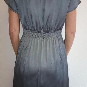 Varetype: Smart grå Vero Moda kjole str M - Vare nr. 300 Farve: Grå  Smart Vero Moda kjole str M Smart skinnende satin i flot grå farve med slå om effekt I fin stand Mål: længde 96 cm talje ca 68 cm   Vægt: ca 165 g  IKKE RYGER HJEM & INGEN HUSDYR.  Sendes med Dao365 til nærmeste udleveringsshop medmindre andet aftales.  Sender gerne flere varer samlet :-)