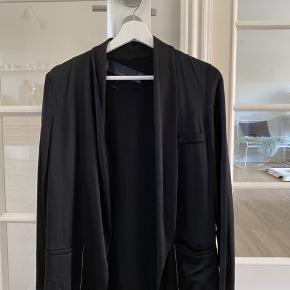 Zara blazer str. XS i sort med hvide sy detaljer og fake lommer foran. Blazeren er gået med, men standen er stadig god.  Der følger et bælte med i samme stof.   Mærket sidder løst i den ene side.