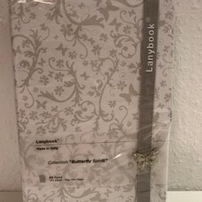 Super Lækker Bog fra Lanybook i A5 størrelse med 192 sider. Bogens sider er linieret og bogens ydre er et smukt mønster i hvide og lysgrå farver🤩 Lanybooks er et italiensk mærke som er kendt for deres lækre kvalitet og unikke design. Bogen har både en lille holder til en kuglepen og en elastik rem med en dekorativ sommerfugl som holder bogen sammen🦋 bogen er uåbnet og derfor i perfekt stand👌 hvem skal være den heldige?