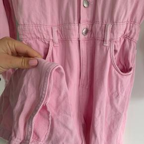 Sælger denne fine lyserøde boilersuit i str M men passer S/M. Den er udsolgt på nettet. Den har elastik i taljen, så den fitter stort set alle kropstyper. Den har små slids på indersiden af anklerne