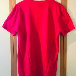 Super frisk lyserød/pink T-shirt med stort print for fra Hugo Boss sælges da den aldrig bliver brugt. T-shirten fremstår som ny, uden huller, pletter el anden form for slitage da den højest har vært båret 3-4 gange siden den blev købt hos magasin i Århus.  Kom med et fair bud