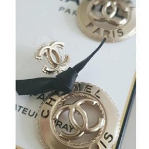 Chanel øreringe, guldfarvede med sort læder. Købt på Vestiaire Collective hvorfra jeg også har ægthedsbevis. Ingen tegn på slid er som nye. Bliver solgt med æske og bevis fra Vestiaire Collective. Dog er æsken ikke en Chanel æske.