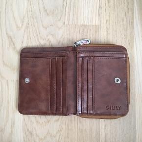 Sød pung fra Oilily med mange rum. Pungen er brugt men pæn. Den har lidt slid på hjørnet og lidt brugsspor ved lynlåsen.