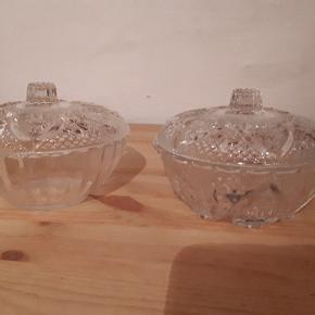 2 små glas bonbonniere. Lågene er ens, men skålene er forskellige. Perfekt stand. 9 cm høje og 13 cm i diameter. Samlet pris. Porto 37 kr