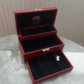 Rødt smykkeskrin  Måler ca. L: 24 cm, B: 15 cm, H: 11 cm.  Brugstegn i bunden (se sidste billede)  Hentes i Roskilde eller sender med DAO mod betaling af fragt.