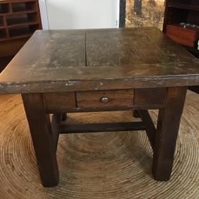 Rustikt gammelt sofabord i gedigent træ sælges. Det kommer med skrammer og brugsspor, hvilket i mine øjne kun er charmerende. Der er en lille skuffe under bordet. Mål: Højde: 53 cm Bordpladen: 66x66 cm