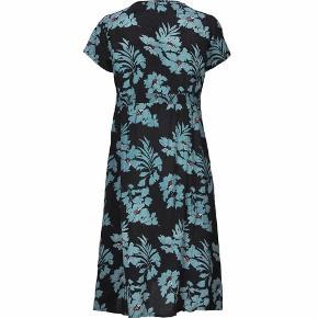 Nibia kjole i marineblå viskose, fast stof, med lyseblå blomster.  Små læg foran på brystet og elastik i taljen på bagsiden. Let taljeret, men løs pasform.  Brugt en enkelt gang. Fremstår som ny.  Lyseblå cardigan og tørklæde i samme mønster sælges også, se separate annoncer.   Bryst: 58 cm Længde: 113 cm.   Sendes med DAO.  Allergivenligt hjem uden tobak eller husdyr.