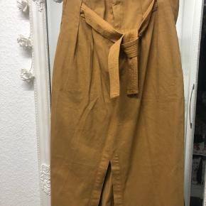 Fin ny højtaljede nederdel i farven mørk karrygul. Aldrig brugt, stadig med prismærke. Str 40