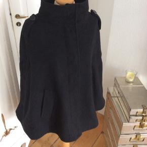 Smuk sort kappe cape fra Gina Tricot med huller til arme. Dybe lommer. Str 38/40. Længde: ca 70 cm Skuldermål: ca 46 cm  Sendes med DAO.Kan evt afhentes i Kbh K ved forudbetaling.