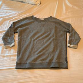 Grå trøje fra Day Birger et Mikkelsen sælges. Str m. Der er sølv glitter i det grå stof og gennemsigtig stof på ryggen.   Næsten ikke brugt og fremstår derfor som ny