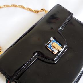 Vintage Gucci taske clutch udført i laklæder og med hardware af forgyldt metal.  Tasken er med kæderem (ca 35cm fra ende-ende), pyntesten ved lukning samt flap og bøjelukning. Indvendigt med 2 rum og 4 sidelommer hvoraf den ene er med lynlås og Gucci knight crest vedhæng.  Dustbag medfølger (se billede i kommentarfelt).   Højde ca 14cm, bredde ca 19cm, dybde ca 4cm.   Fremstår med aldersrelaterede brugsspor da den er vintage. (Små spots bagpå tasken, se billede). Se flere billeder i kommentarfelt! Dustbag medfølger men er beskidt.   Handler kun med mobilepay. Tasken kan afhentes efter aftale på Frederiksberg/Hellerup.