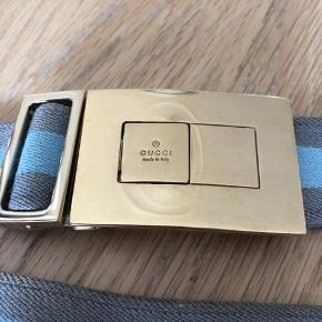 Gucci bælte i elastik, og kan derfor bruges almindeligt i bukser om som waist belt, da længden kan justeres  Mål 85 cm i fuld længde   Har små ridser som ses på billederne