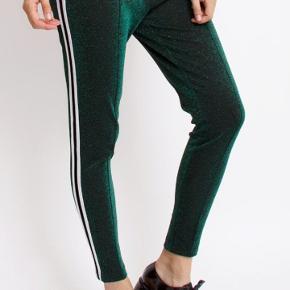 grønn glimmer bukser med detalje i side. de har kun været brugt et par gange. Mp.150kr.plus porto. handler gerne med mobilepay.