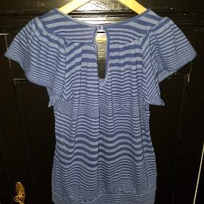 Sød stribet t-shirt med bredt panel forneden, der gør den  poser lidt. Dertil løse ærmer og en fin detalje med åbning og slået knap på ryggen.