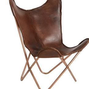 Butterfly stol sælges. Det første billede er taget fra nettet, da min egen stol er skilt ad (så den er nem at have med). Det andet billede er min stol i vores gamle lejlighed.  Den er med kobberfarvede ben, og selve læderet er i brunlige farver med et lidt slidt look (på en fed måde!), og den er helt enorm fed med et skind i!  Jeg har selv købt den brugt for 950 kr.  ⭐️⭐️⭐️ BYD!