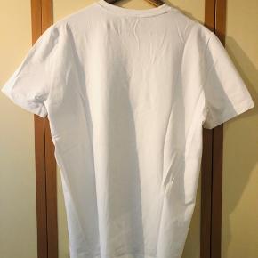 Frisk hvid T-shirt fra Armani med stort log for i guld sælges da den aldrig har vært kommet i brug siden den blev købt. T-shirten er fremstillet i det behagelige streg(?) stof så den sidder tæt ind på kroppen.  Giv et fair bud