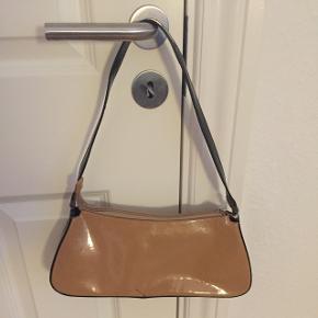 """""""Gucci""""taske - ikke ægte. Rigtig fin laktaske i sort & nude. Skulder- eller håndtaske. Rigtig pæn stand, der er kun en enkelt sort mærke (se sidste foto), ej forsøgt fjernet. Indvendig er den helt som ny. Rum med lynlås samt et par lommer. Byd blot! Hurtig handel prioriteres ... Jeg sender gerne!"""