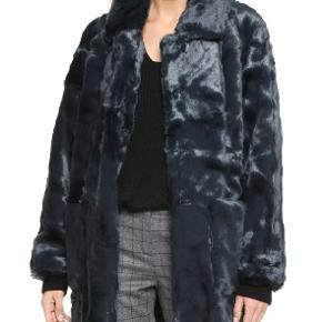 """Blødeste Ganni faux fur i mørkeblå, måske har den et skær af petroleum?   Modellen hedder Liberty st. Fur.   Jakken er næsten ikke brugt, men har desværre mistet den nederste knap/hægt.  Det er svært at få et ordentlig billede af min egen jakke i stue- og decemberlyset, men hvis du er meget interesseret tager jeg den gerne ud i """"dagslyset"""" og tager et billede.  Jeg er selv XL og den har passet fint :-)"""