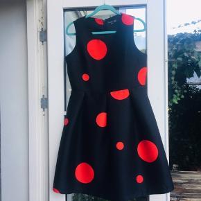 Smuk kjole med masser af vidde i skørtet, figursyet for oven. Sort med røde dots. Str large/40