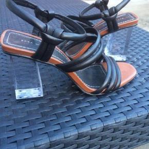 """Varetype: Heels Farve: Sort Hælhøjde: 8 cm Oprindelig købspris: 700 kr.  Totalt skønne sandaler! Læderremme og gennemsigtig """"glas""""hæl! Aldrig brugt"""