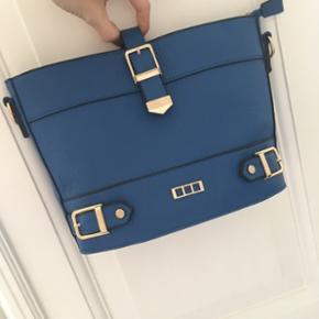 Fedeste blå taske med rem. Den er fuldstændig ubrugt og fejler derfor intet.    Se gerne mine andre annoncer med mærker fra bla. Soaked in Luxury, Zara, Ganni, Alexander Wang, ASOS, Envii, H&M og mange flere.