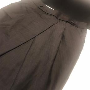 Sort nederdel med tynd Strib. Lidt læg foran og sjov detalje med 2 knapper i taljen. Så fin en nederdel.