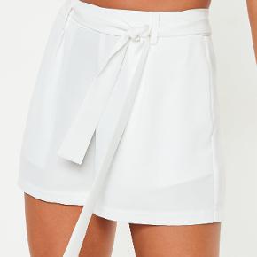 Shorts, Missguided, str. 38, Cremefarvet hvid, Ubrugt Super feminine og sommerlige shorts lige til at pakke i kufferten. Med sidelommer, lynlås bagpå, bæltestropper og aftageligt bælte. Har lagt et par billeder ind af modellen i sort, så man bedre kan se hvordan de sidder på, men dem jeg sælger er hvide. De er helt nye og ubrugte med mærkesedler. Nypris: Cirka 250 kroner. Eventuel fragt lægges oveni: 37 med DAO til nærmeste posthus/butik Foretrækker betaling over mobilepay, da jeg gerne vil være fri for gebyrer :-)
