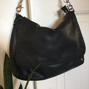 Taske i skind med sølv hardware fra Depeche.  Kan bruges både som skuldertaske og brossbody, da der medfølger en justerbar læderrem.   Foer i viskose