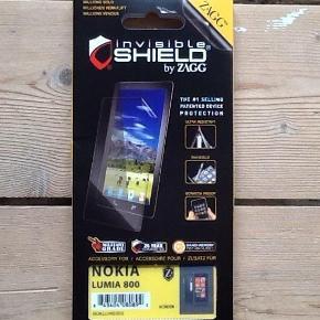 """Helt ny beskyttelsesfilm til Nokia Lumia 800. Kassen har aldrig været åben.  På produktets hjemmeside står der:  - Slidstærk - Selvrensende egenskab giver utrolig modstandsdygtighed mod ridser og skader, og forlænger din enheds levetid - Dækning - Større elasticitet og fleksibiltet gør at ZAGG invisibleSHIELD er designet til at dække hjørner og kanter på din enhed bedre end dens konkurrenter. - Let installation - Den forbedrede elasticitet giver også lettere installation - Tabes ikke let - Forbedret greb gør det lettere at holde fast i din dyrebare enhed - Reduktion af genskin - ZAGG invisibleSHIELD giver din enhed et svagt """"orange skær"""", der bryder genskin og reducerer fingeraftryk, samtidig med at du stadig har en opløselig skærm som ses klart.  B-Porto = 14,50 kr.  Beskyttelsesfilm - skærm beskytter - Nokia Lumia 800 Farve: - Oprindelig købspris: 199 kr."""