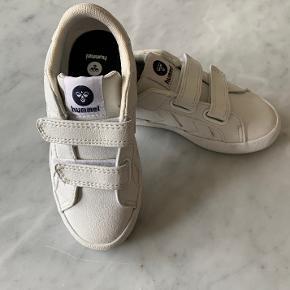 Smarte hvide sneakers/kondisko fra Hummel med 2 velcro lukninger. God pasform. Str. 24. Brugt lidt, men er stadig i super fin stand. Kan bruges både til drenge og piger for et cool look. Købt til 599,00.