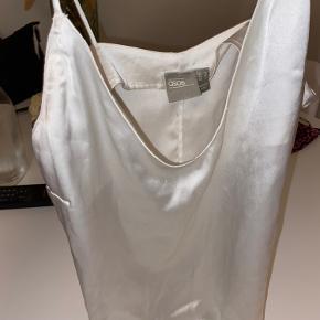 Fin hvid top som kun er prøvet på. Den har en lidt dyb udskæring ved brystet.