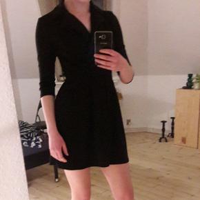 Elegant kjole med 'skjorteformet' halsudskæring. Kan bruges både med og uden det medfølgende bånd.
