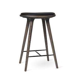 Mater, High stool, Sirka Grey Oak. Håndlavet indisk design. Fik sit gennembrud i lagkagehuset, hvor den bliver brugt i alle deres forretninger. Træ og læder.Mål:  H: 66 cm. & 74 cm.  Nypris 6.500  Har 4 stk.