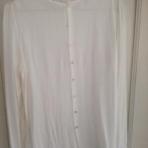 Sød cremefarvet skjorte med knapper ned af ryggen. Haft på 1 gang, 100 % viskose.