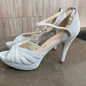Flot stillet / sandal på hæl, brugt meget få gange og fremstår derfor i perfekt stand. Højden er 8 cm, med 2 cm plateau foran, så reelt 6 cm.  Kan afhentes i Aalborg