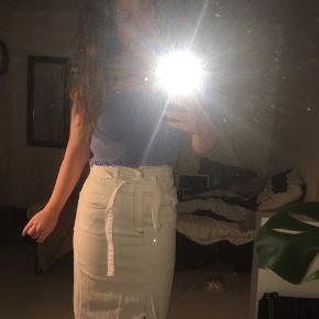Jeg sælger denne lange denim nederdel, da jeg aldrig har fået den brugt. Den kan bindes i taljen med et bælte som medfølger, og kan derfor også passes af en størrelse small